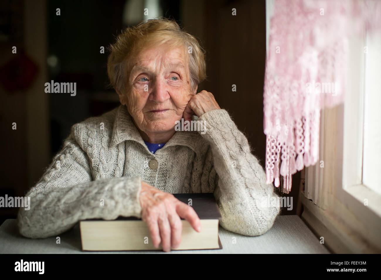 Eine ältere Frau sitzt mit einem großen Buch neben dem Fenster. Stockbild