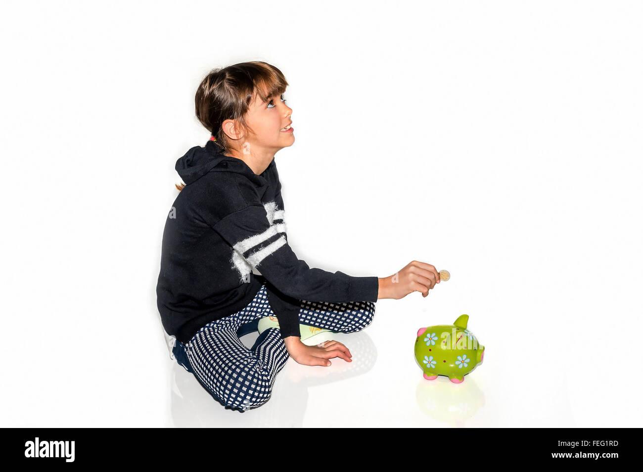 Kleines Mädchen sparen Geld im Sparschwein Stockbild