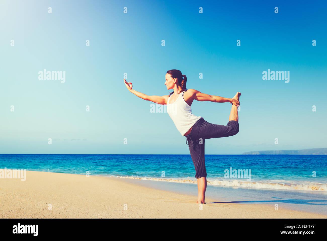 Gesunder Lifestyle-Konzept, schöne junge Frau dehnen praktizieren Yoga am Strand Stockbild