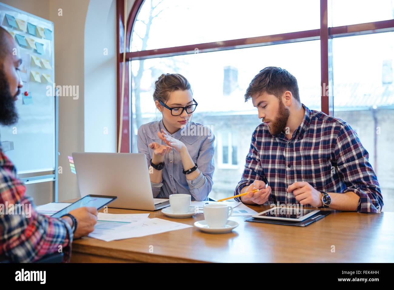 Multiethnische Gruppe von jungen Geschäftsleuten mit Brainstorming in Büro Stockbild