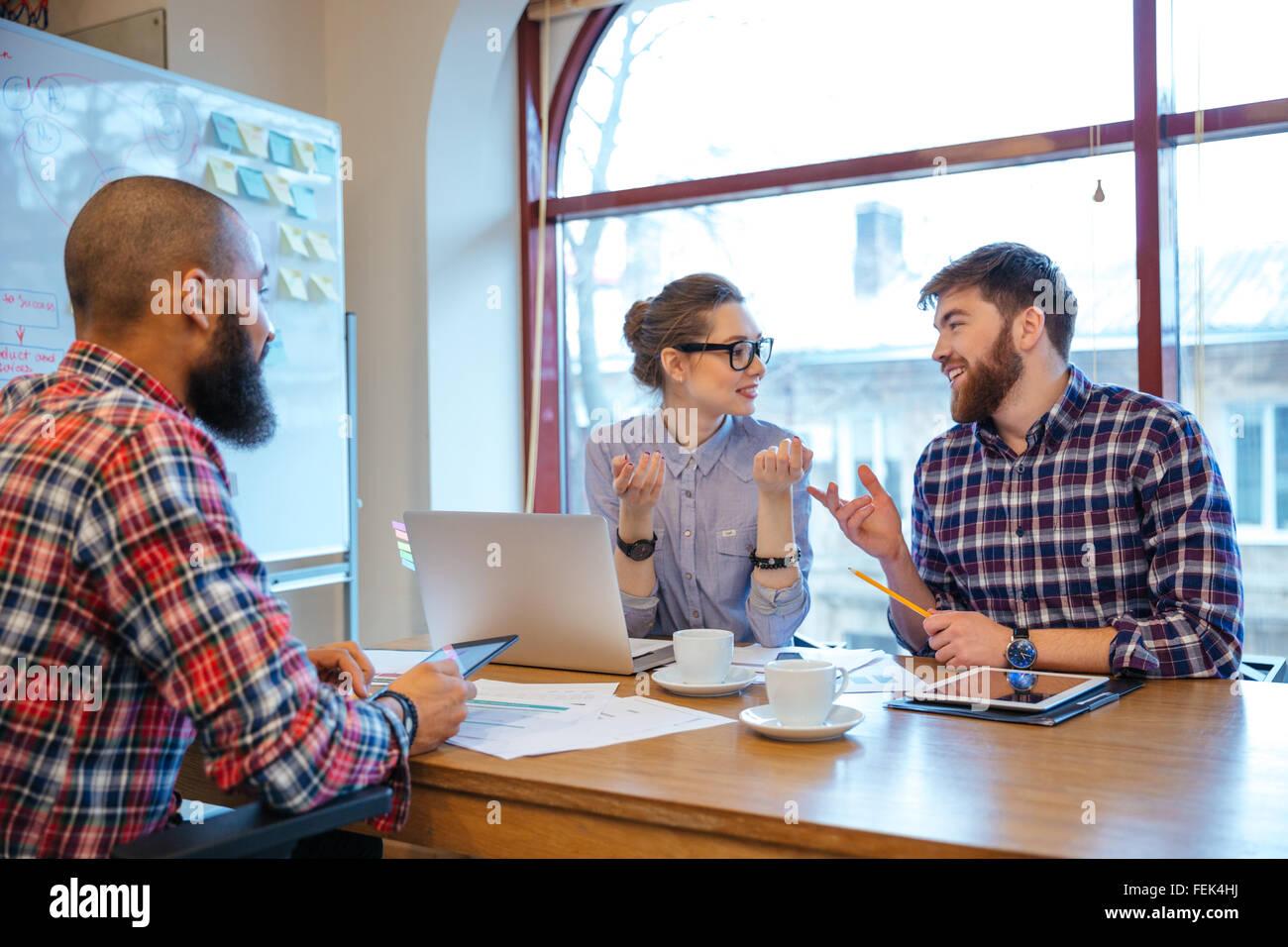 Multiethnische Gruppe von fröhlichen Menschen, die auf Geschäftstreffen zusammen arbeiten Stockbild