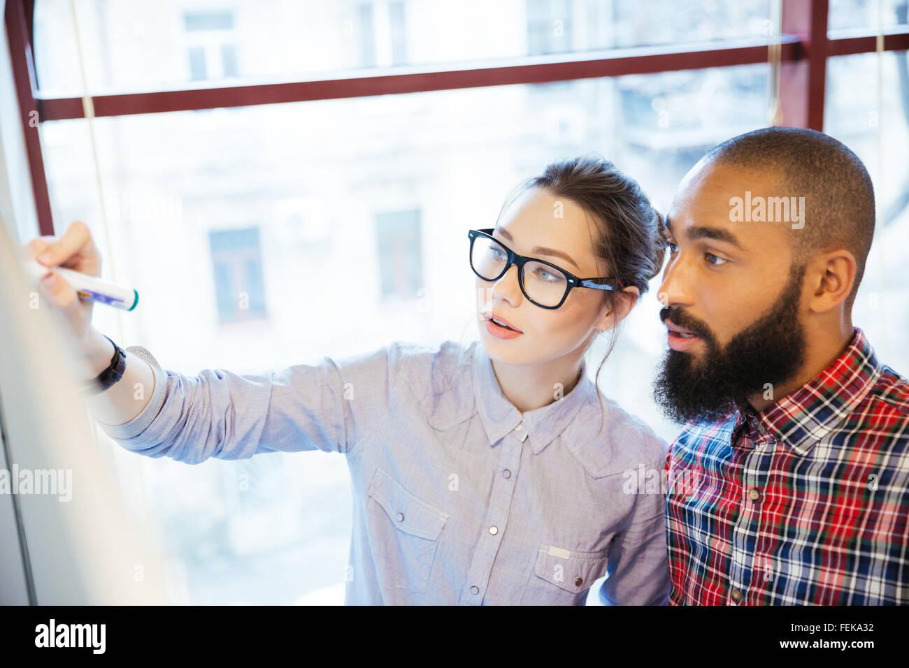 Junge Geschäftsleute mit Whiteboard im Büro Stockbild