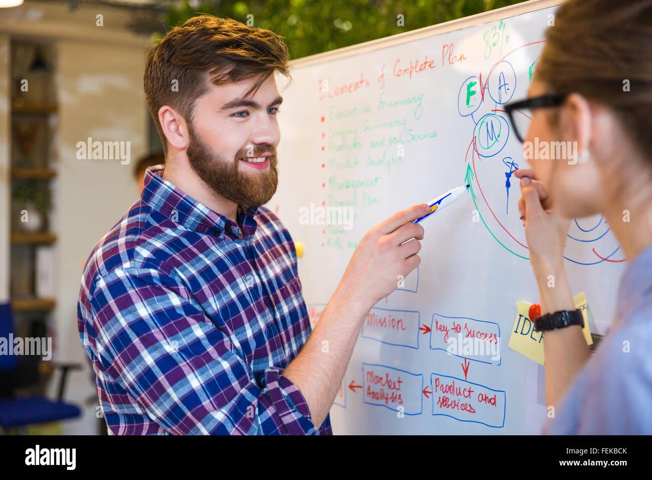 Zwei Jugendliche diskutieren über Business plan im Büro Stockbild