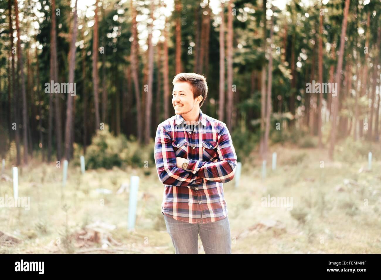 Glücklicher Mann stehend mit verschränkten im Wald Stockbild