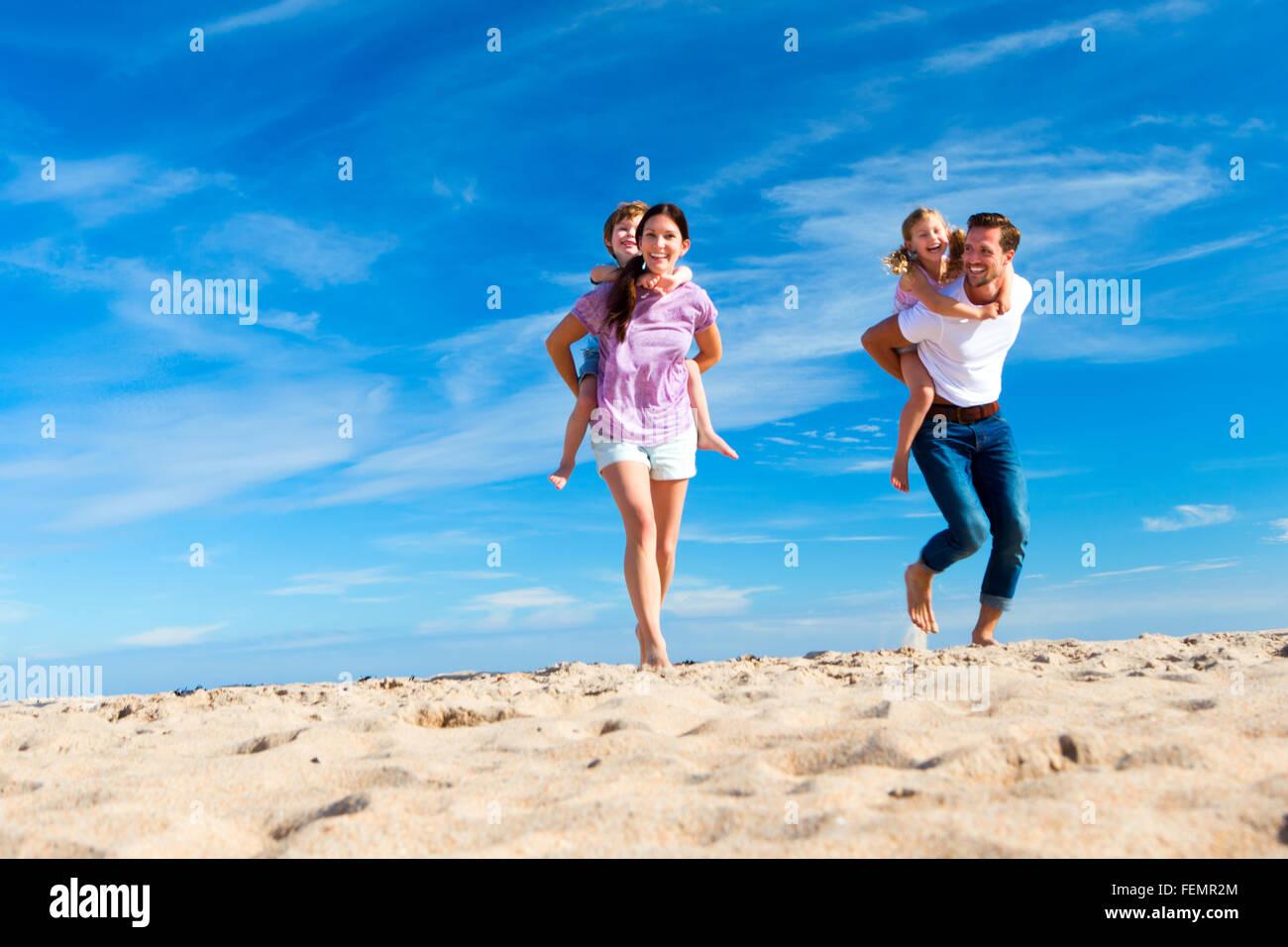 Mutter und Vater Huckepack, ihren Sohn und Tochter am Strand. Stockbild