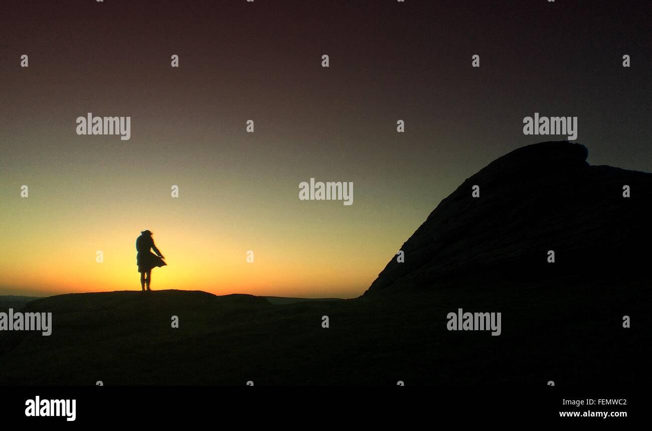 Silhouette der Frau stehen auf Felsen Stockbild