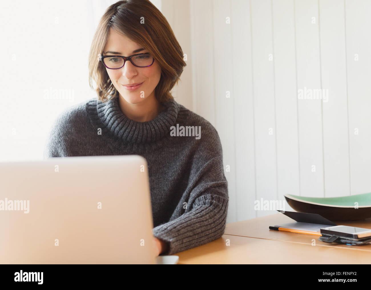 Brünette Frau in Pullover mit Laptop am Tisch Stockbild
