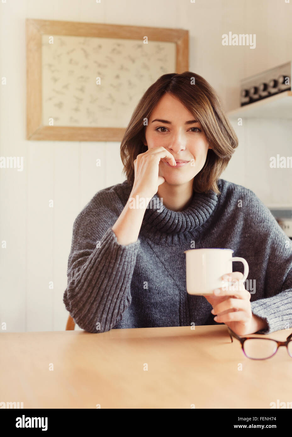 Porträt selbstbewusste Brünette Frau trinken Kaffee am Tisch Stockbild
