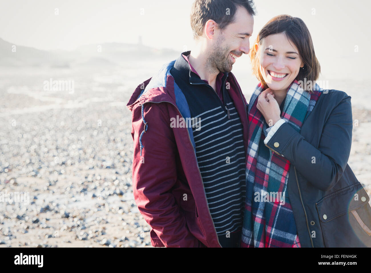 Lächelnde Brünette Pärchen stehen an sonnigen felsigen Strand Stockbild