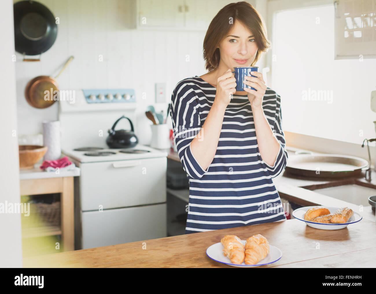 Brünette Frau Kaffeetrinken in Küche Stockbild