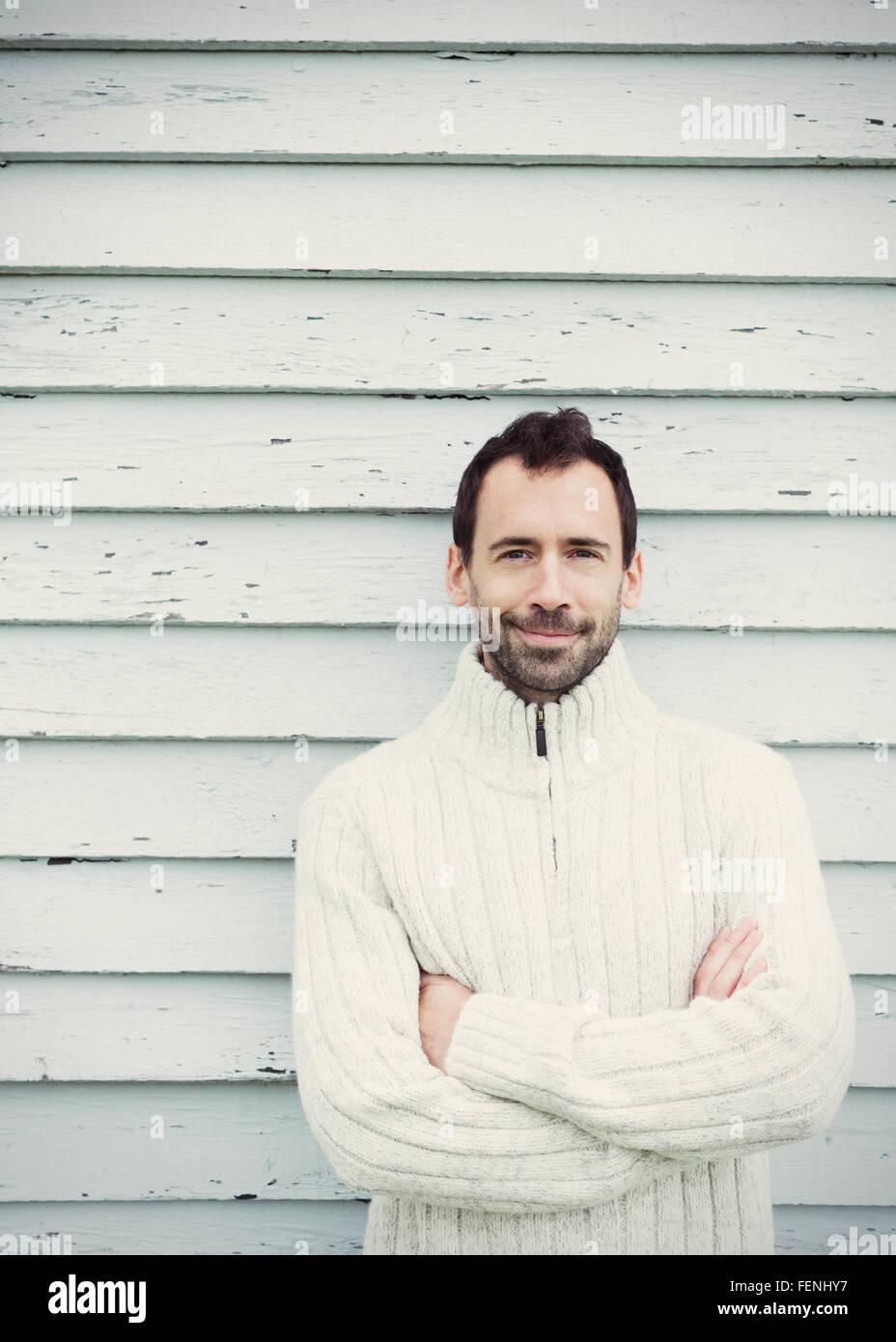 Porträt Brünette Mann im Pullover mit verschränkten Armen Stockbild