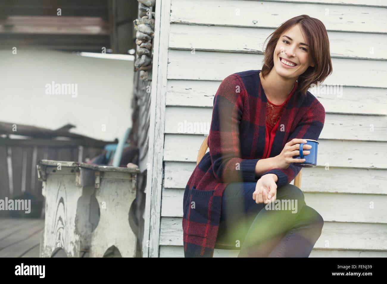 Porträt lächelnde Brünette Frau Kaffeetrinken auf Veranda Stockbild