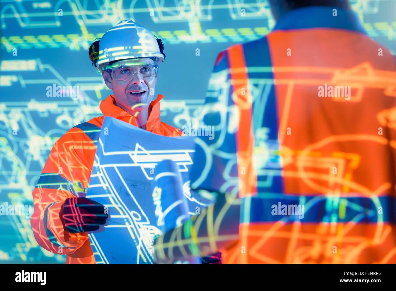 Ingenieure mit Blaupausen und projizierte Pläne Stockfoto