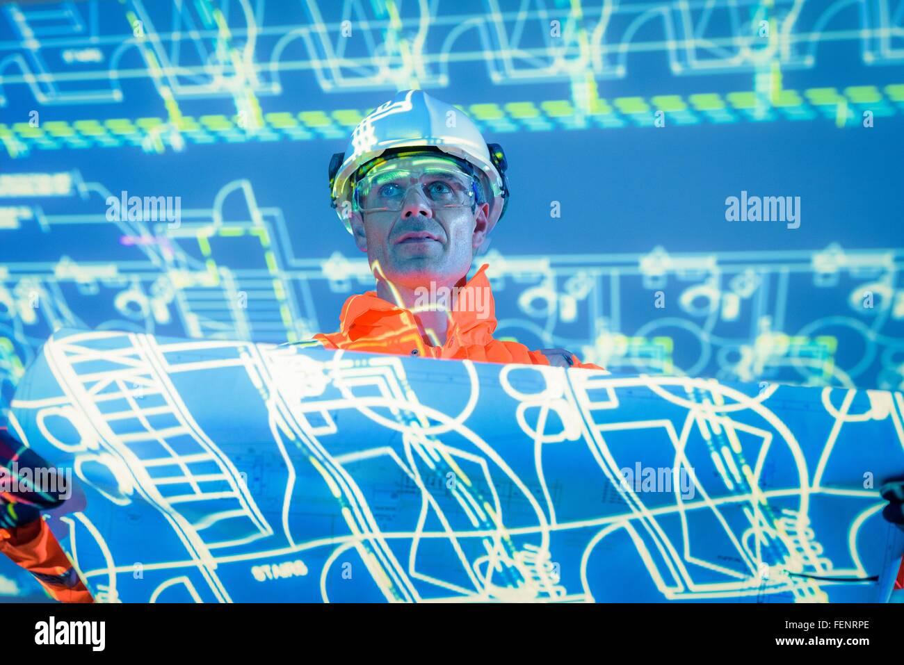 Ingenieur mit Blueprint und projizierte Pläne Stockbild