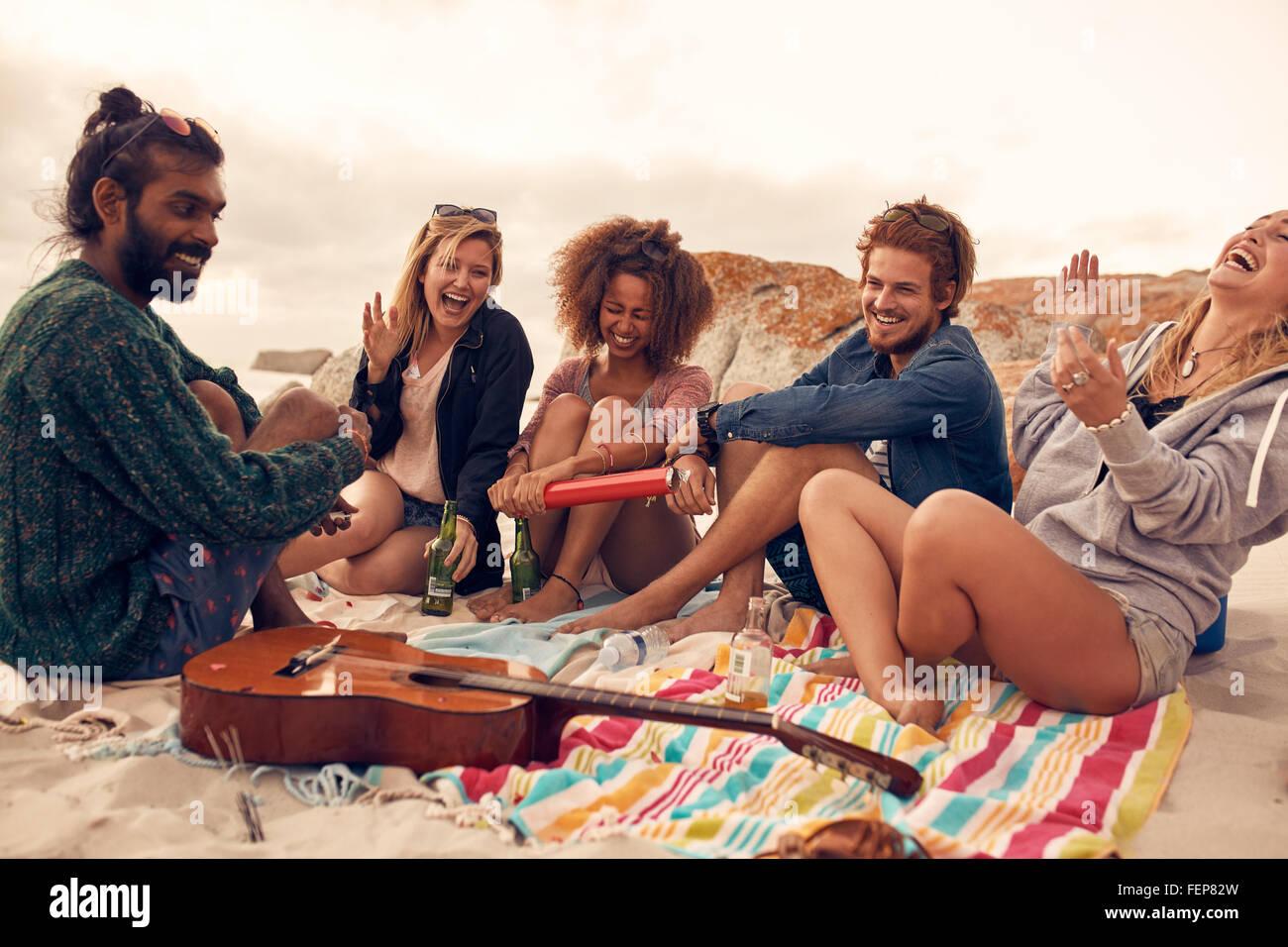 Gruppe von jungen Freunden gemeinsam auf eine Beach-Party feiern. Junge Menschen, die Neujahrsfeier am Meer. Stockbild