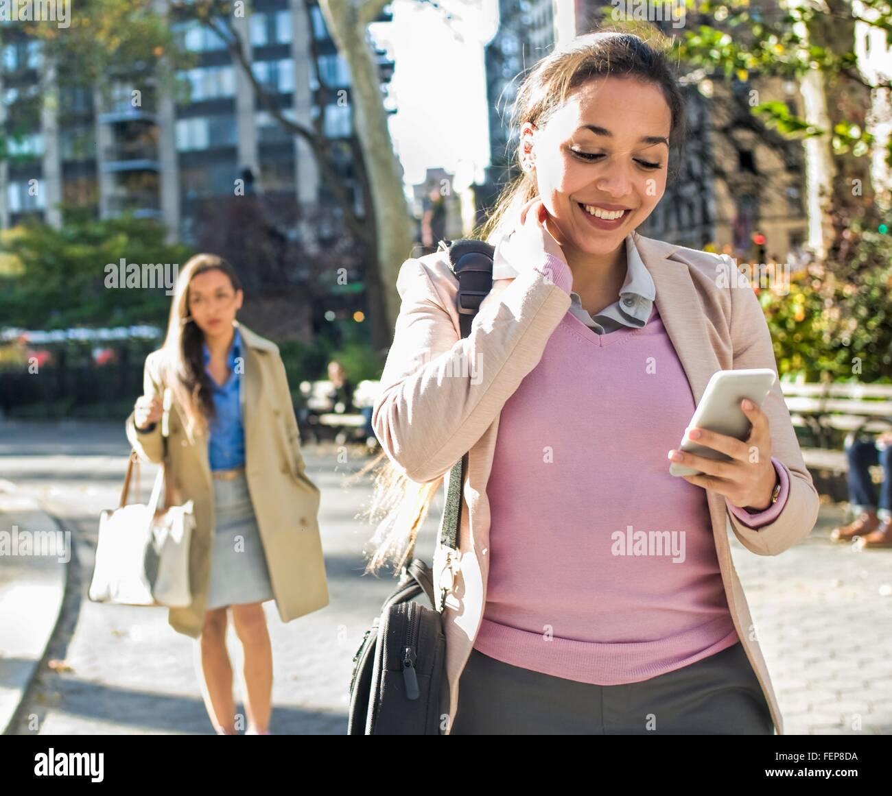 Junge Frau, die Smartphone-Texte zu lesen, während durch den Stadtpark zu Fuß Stockfoto