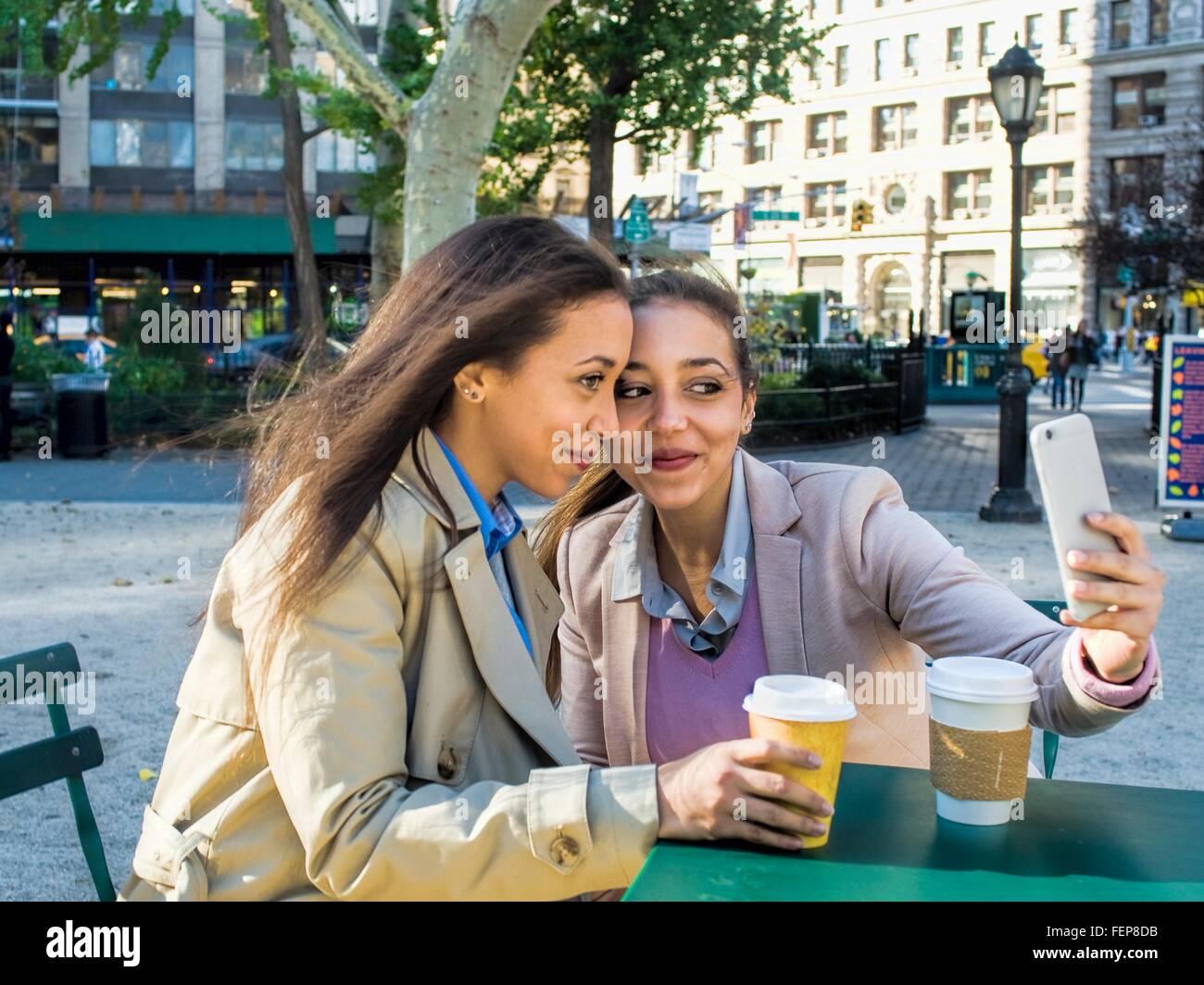 Junge Erwachsene weibliche Zwillinge nehmen Selfie im Stadtpark Stockbild