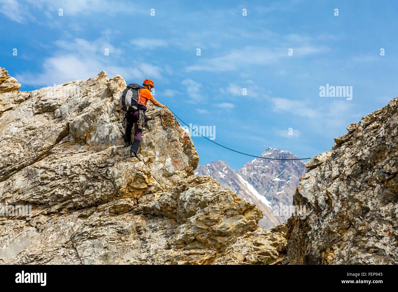 Tapferer Mann klettert felsigen Grat Stockbild