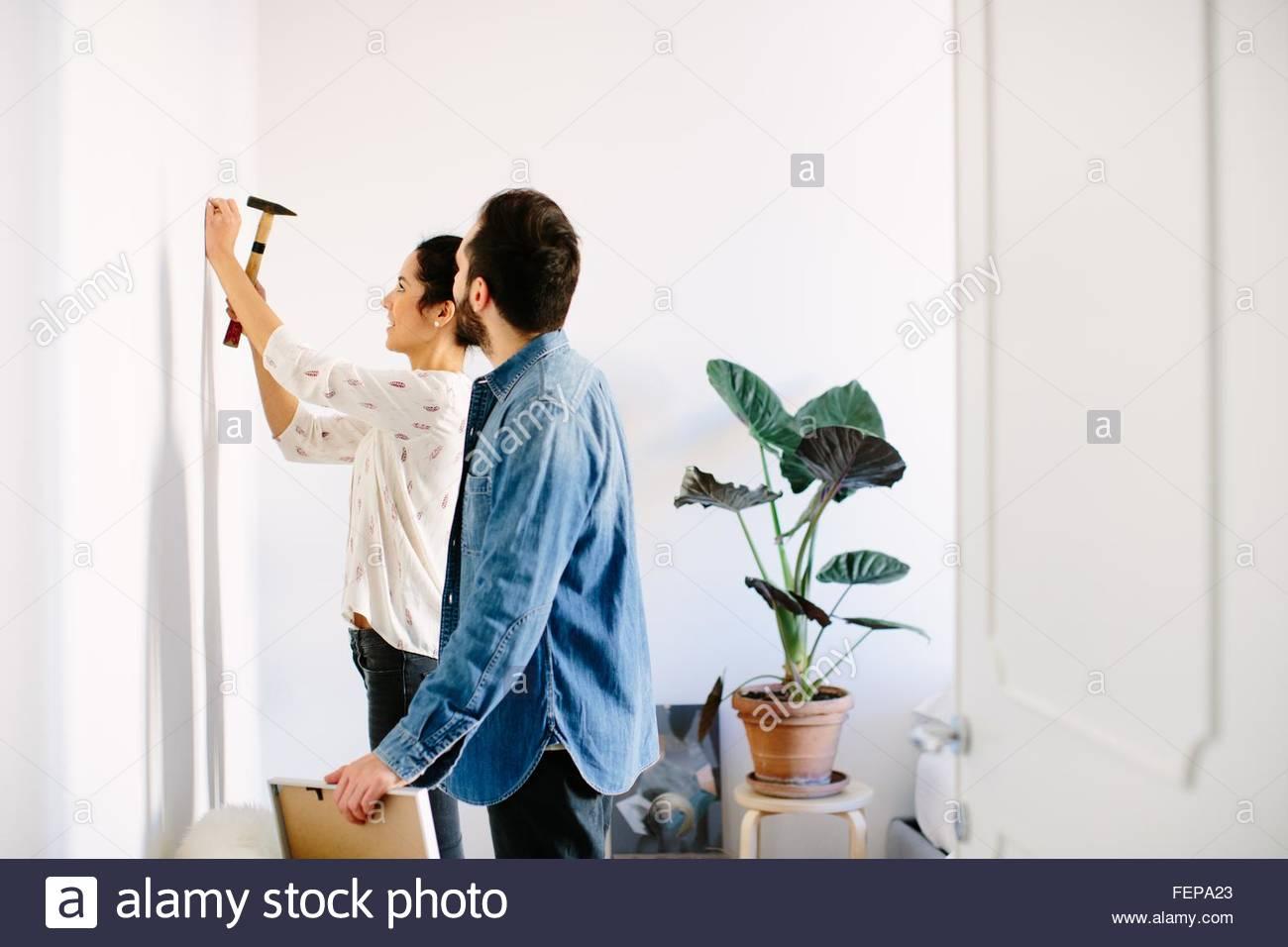 Junges Paar Hämmern in Nagel für gerahmte Bild im Wohnzimmer ...