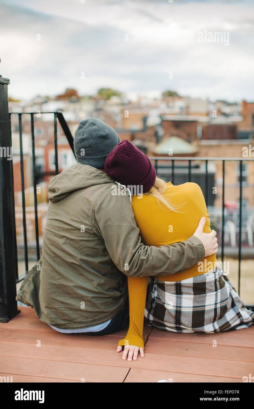 Junges Paar sitzt mit Blick vom Stadt-Dachterrasse Stockbild