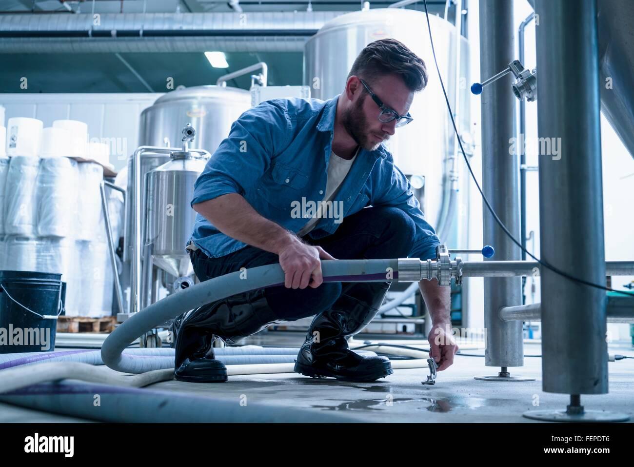 Junger Mann in der Brauerei nach unten Anschluss Rohr hocken Stockbild