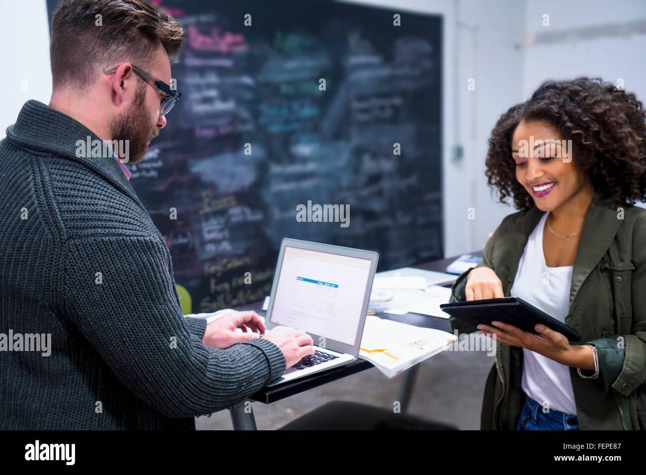 Kolleginnen und Kollegen im Arbeitsplatz über digitale Tablet und Laptop lächelnd Stockbild