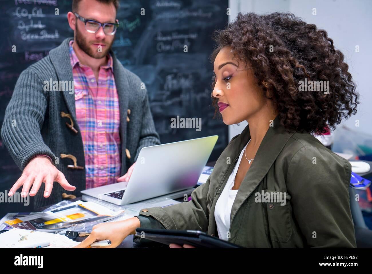 Kolleginnen und Kollegen im Arbeitsplatz über digitale Tablet und Notebook Stockbild