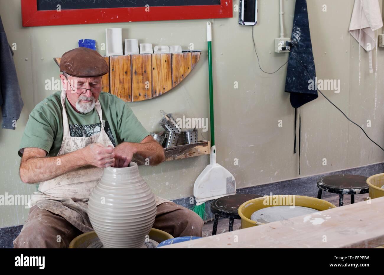 Potter mit flachen Mütze sitzt an der Töpferscheibe Gestaltung Ton vase Stockfoto