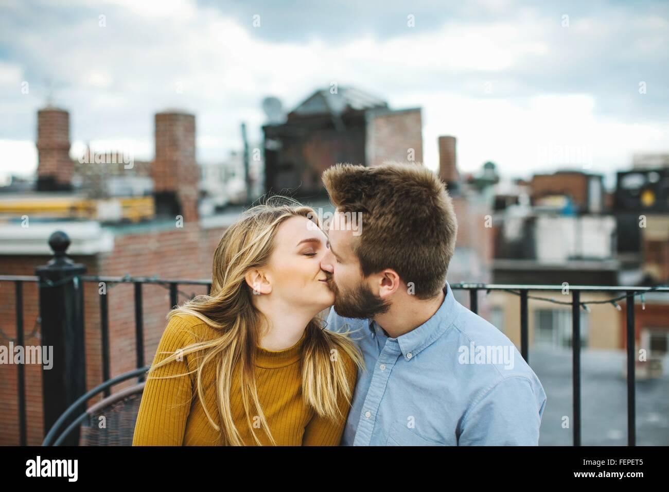 Romantische junge Paar küssen auf Stadt-Dachterrasse Stockbild