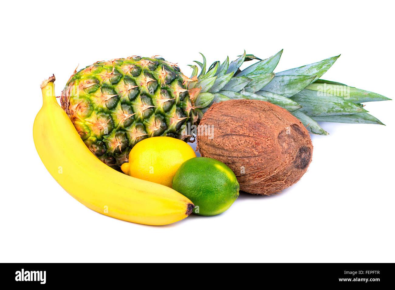 Tropische Früchte wie Bananen, Ananas, Kokos, Zitrone, Kalk isoliert auf weißem Hintergrund Stockbild