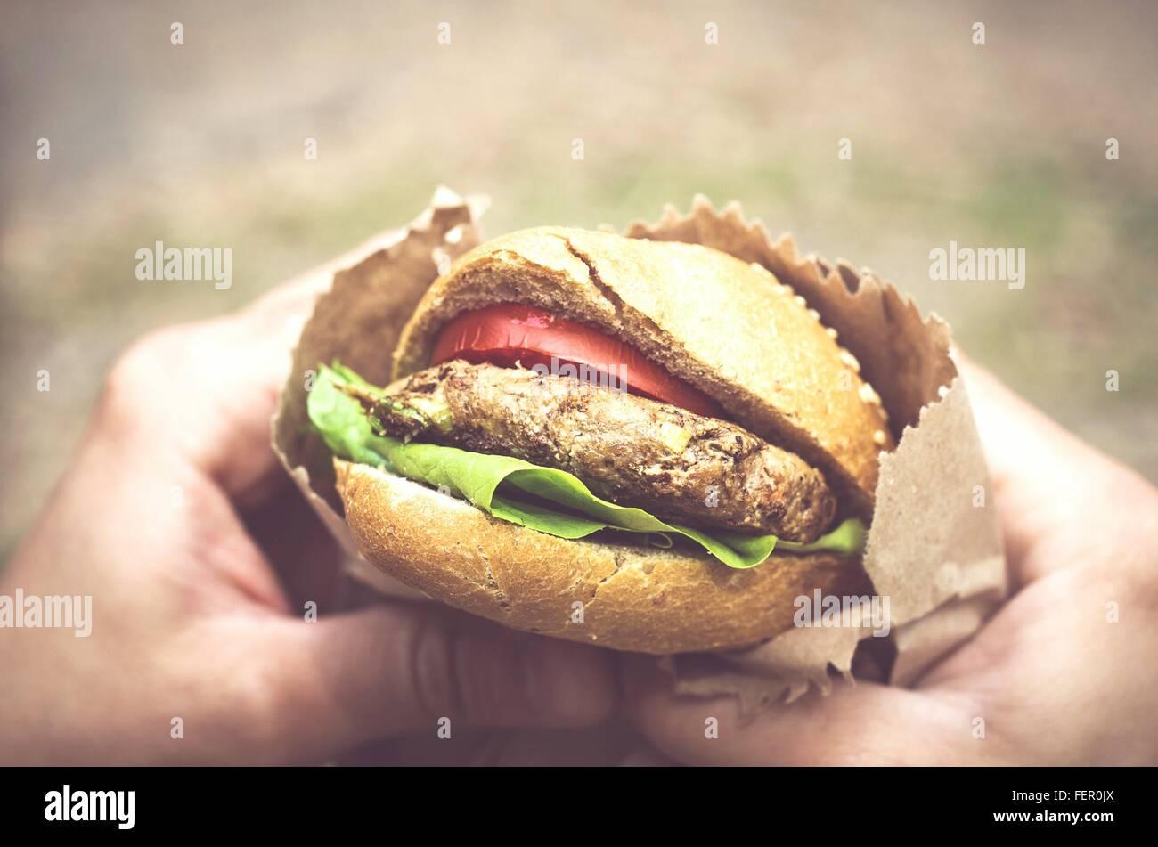 Nahaufnahme von Händen mit Hamburger Stockbild