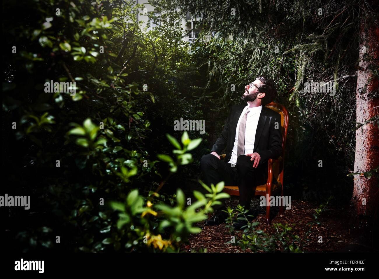 Mann trägt Anzug In Hof auf Stuhl sitzend und nachschlagen Stockbild