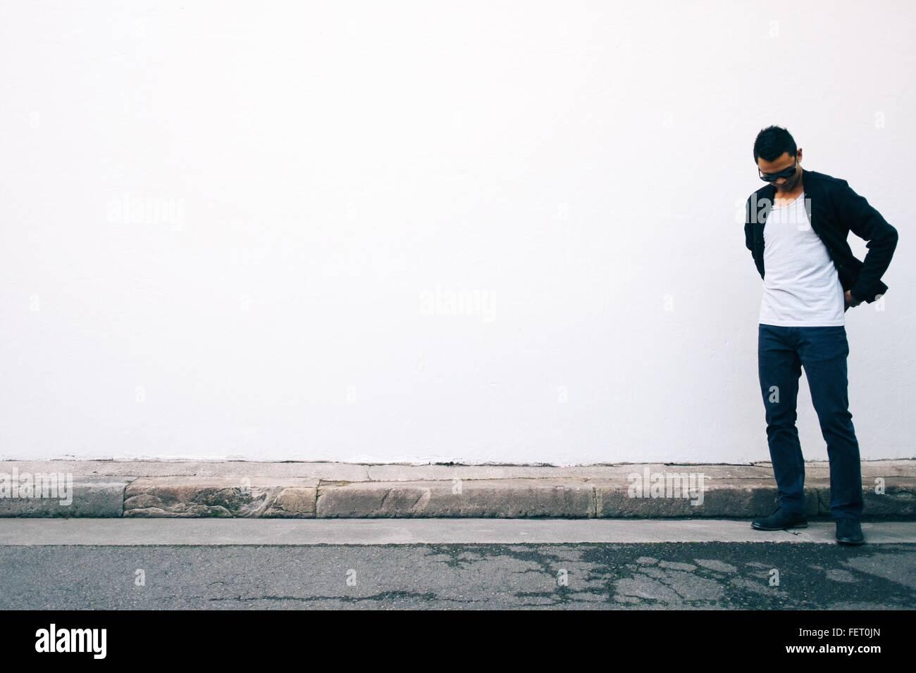 Junger Mann auf der Suche nach unten stehend gegen weiße Wand Stockbild