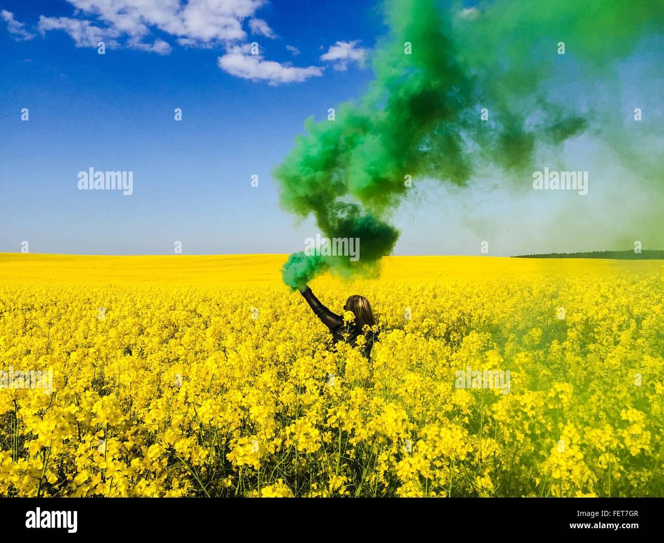 Grüner Rauch ausstoßen von Frau Hand mit Distress Flare auf Raps Feld Stockbild