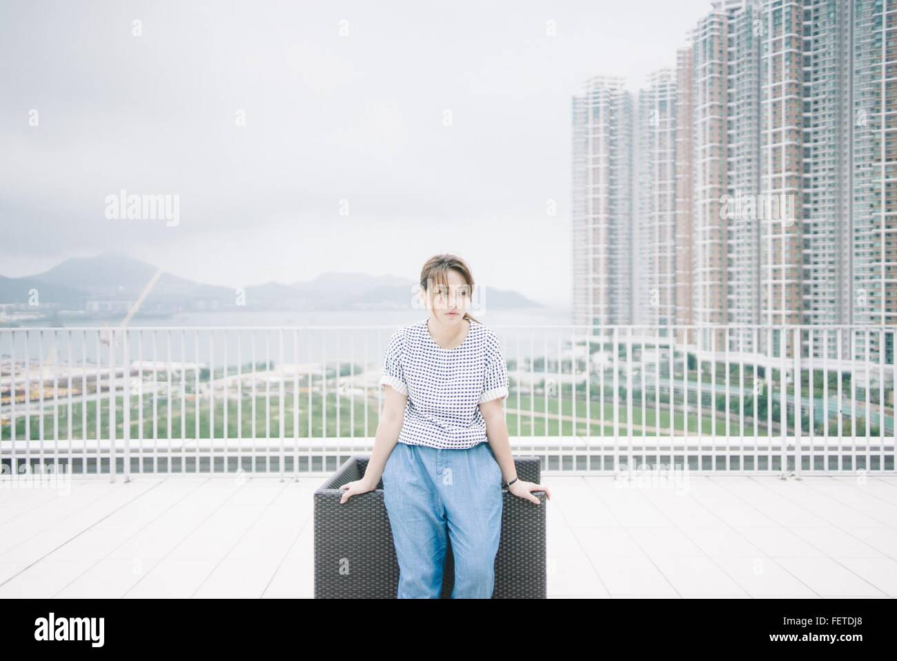 Nachdenkliche Frau lehnt sich vom Stuhl gegen moderne Gebäude Stockbild