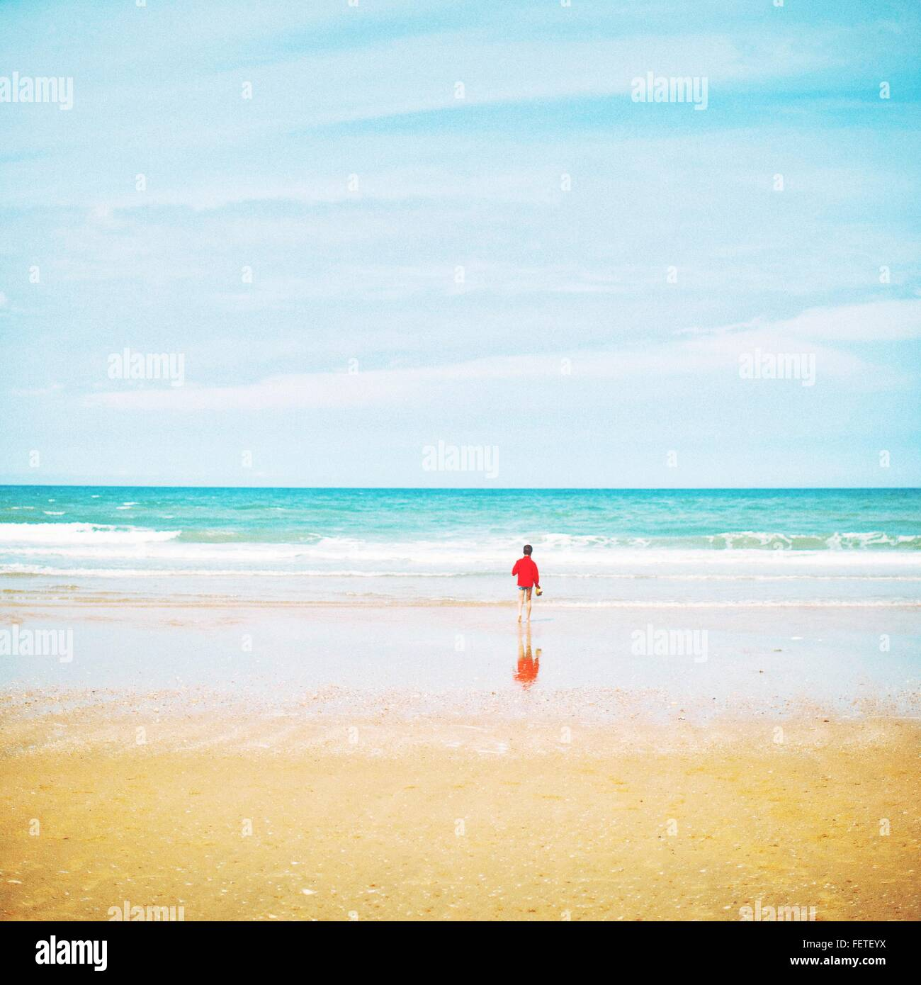 Rückansicht der Person im roten Top, Türkis Seascape, Sand im Vordergrund Stockbild