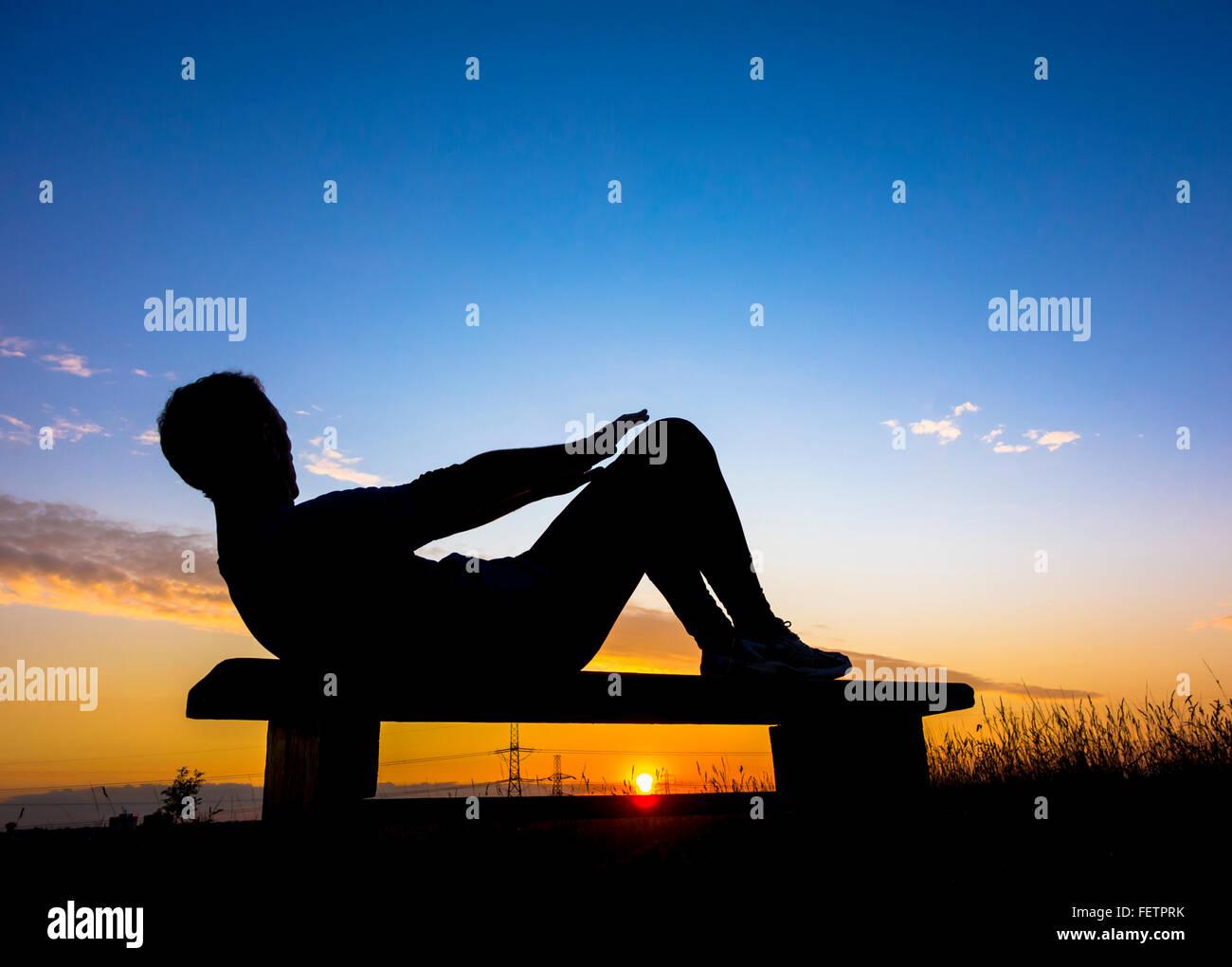 Jogger Erwärmung tun Sit Ups bei Sonnenuntergang in Woodland Park. Großbritannien Stockbild