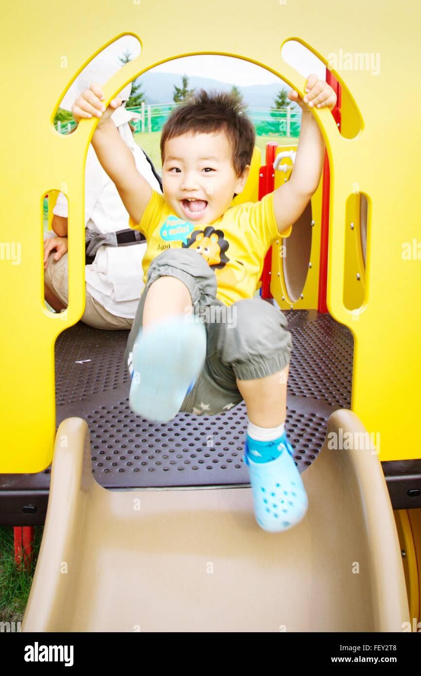 Porträt der fröhliche junge auf Rutschbahn Stockbild