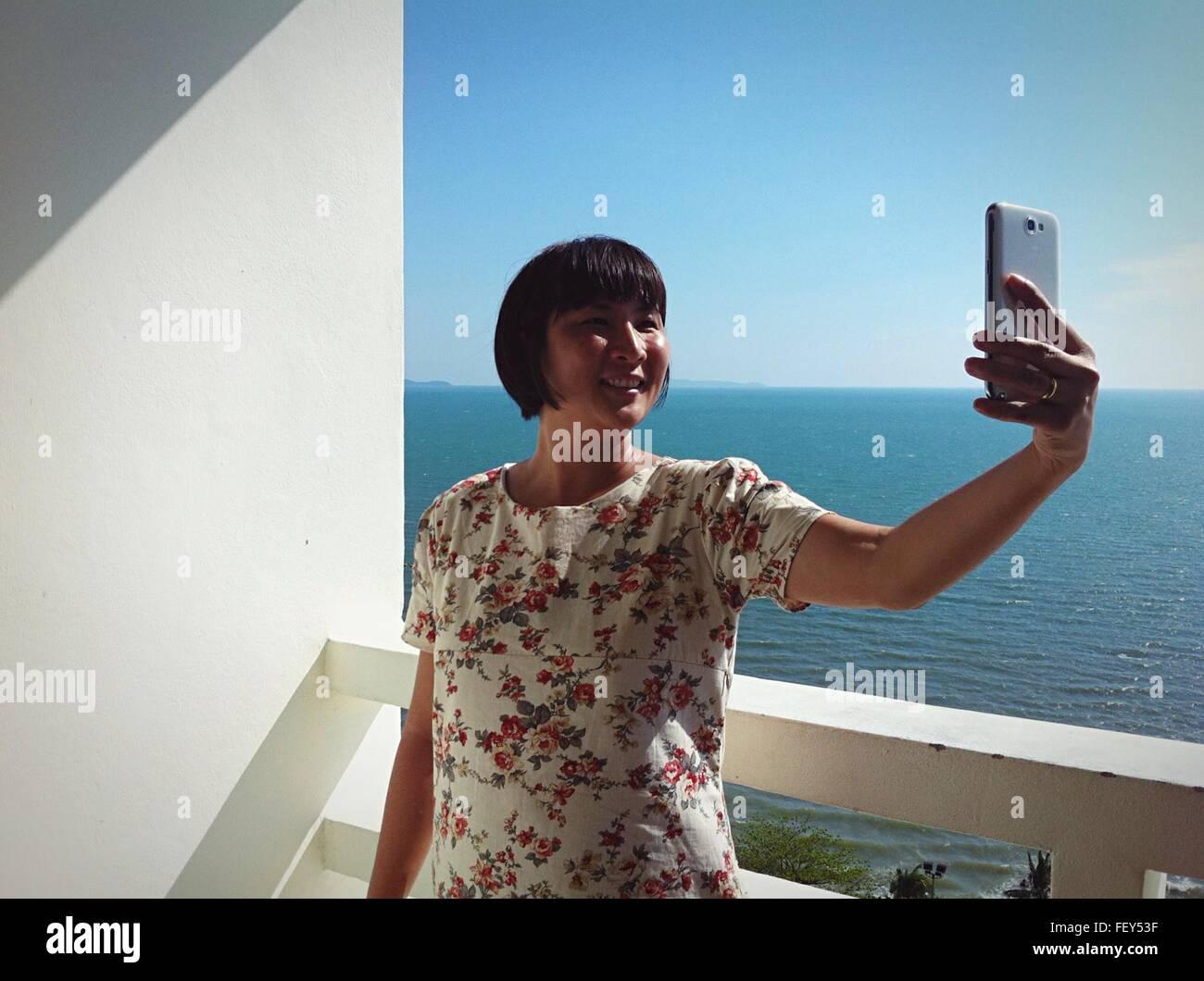 Glückliche junge Frau nehmen Selfie gegen Wand Stockfoto