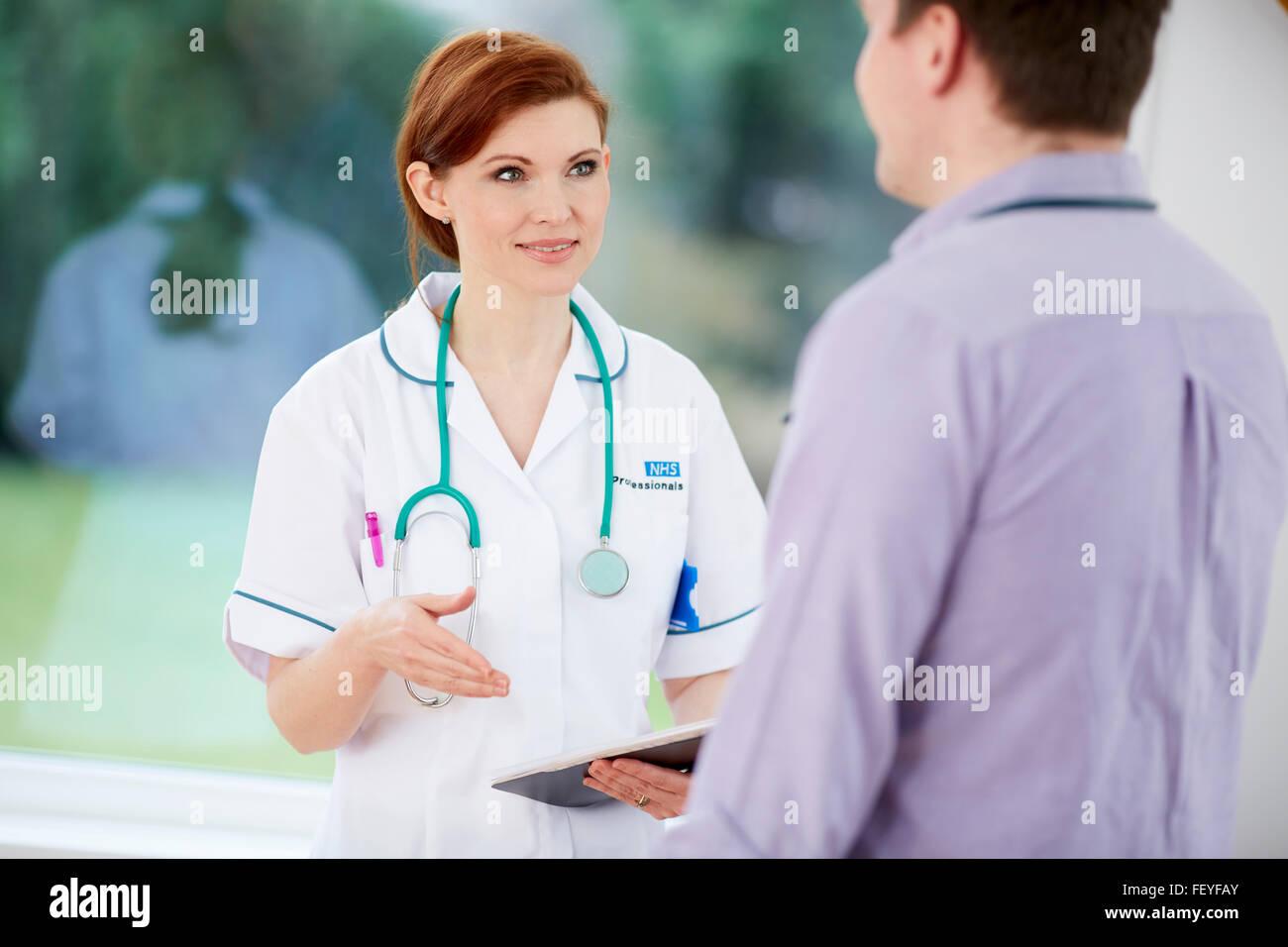 Arzt und Krankenschwester diskutieren Notizen Stockbild