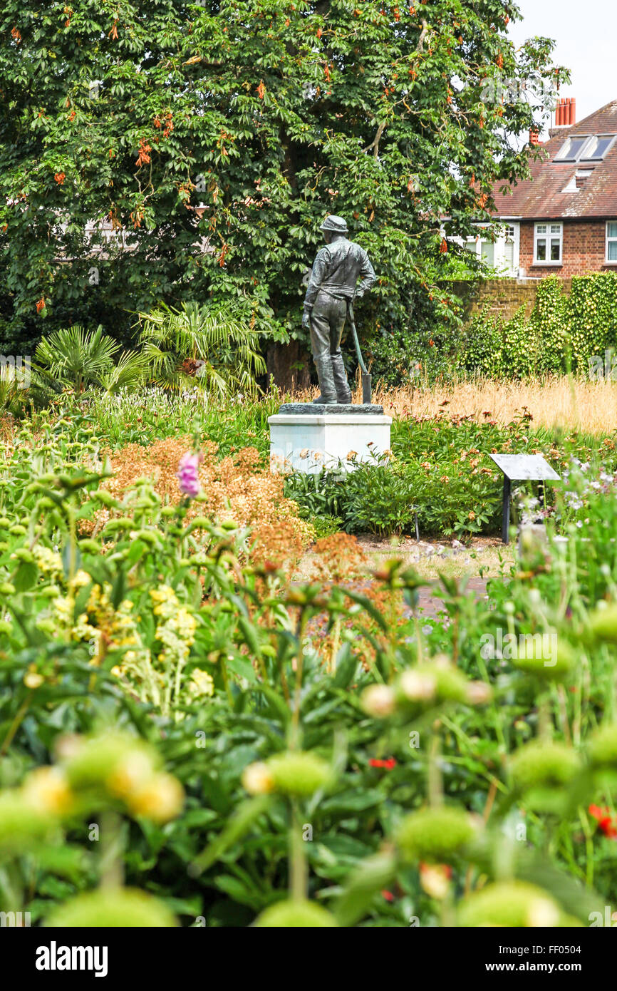Bronze-Statue eines jungen Mannes mit einer Schaufel berechtigt in den Bereichen von Arthur G. Atkinson Kew Botanic Stockbild