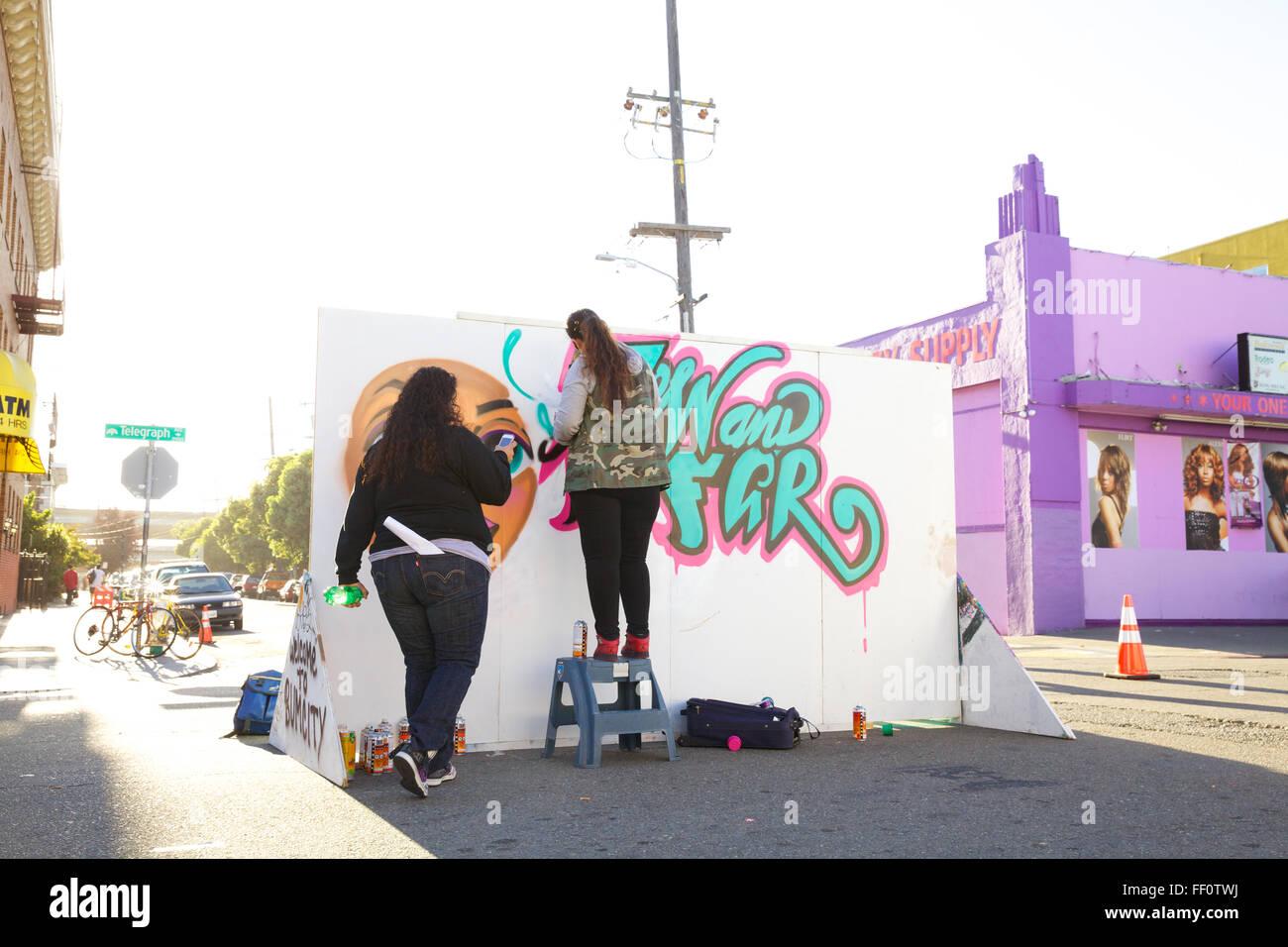 Zwei junge KünstlerInnen Sprühfarbe ein Wandbild auf der Telegraph Avenue in Oakland, Kalifornien. Stockbild