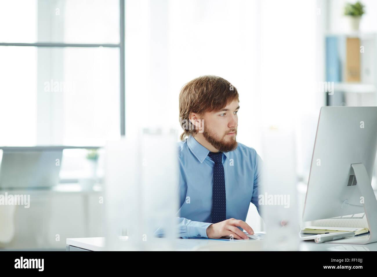 Ernst junger Geschäftsmann Blick auf Daten auf Monitor im Büro Stockfoto