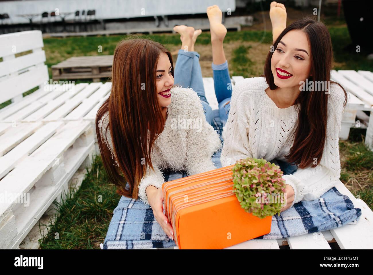 Mädchen auf der Bank liegen und geben sich gegenseitig Geschenke Stockbild