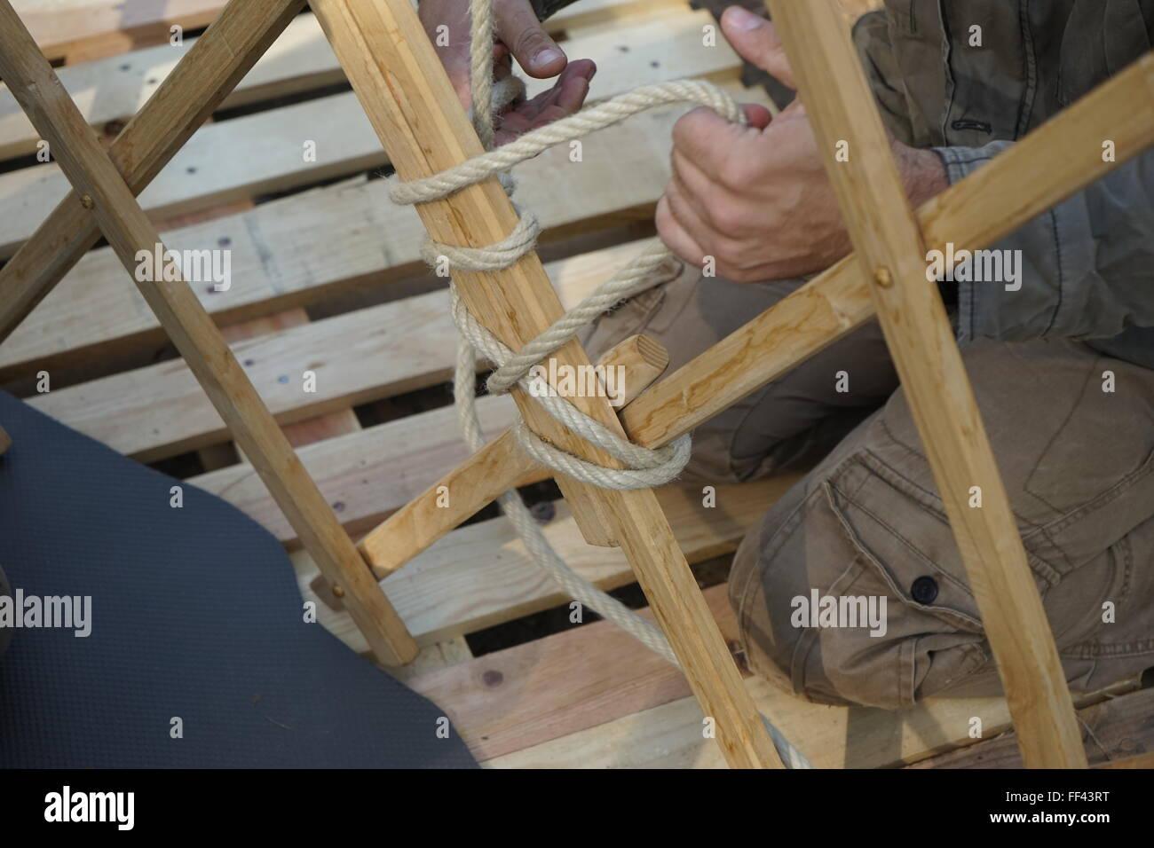 Händen des männlichen Bauherren. Männer bauen asiatische Jurte ...