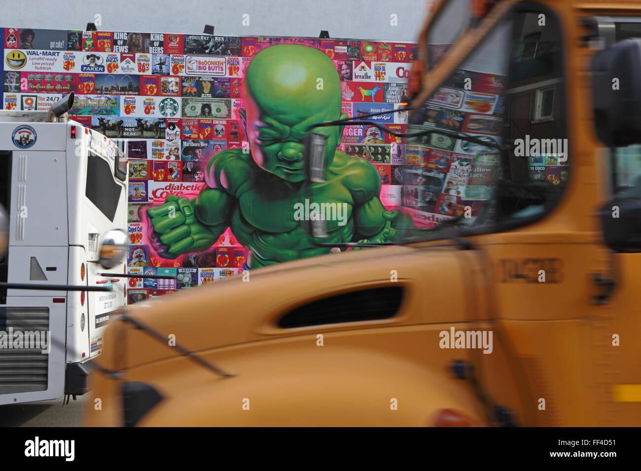 Ein gelber Schulbus fährt vorbei eine Collage von Ron English an der Bowery Wandbild Wand auf der Houston Street Stockfoto