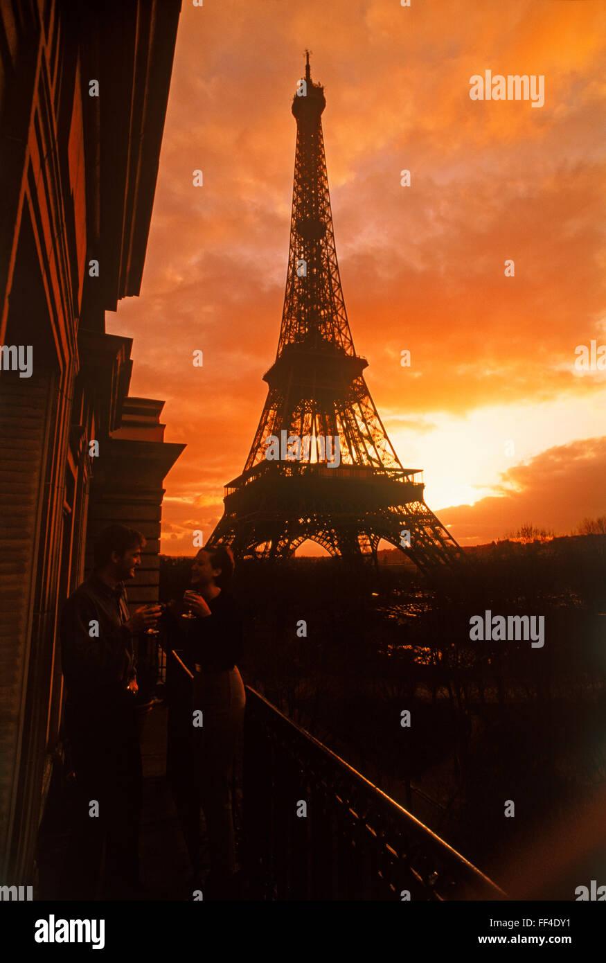 Paar auf Wohnung Balkon genießen Sonnenuntergang Getränk unter dramatischen Himmel nahe dem Eiffelturm Stockbild