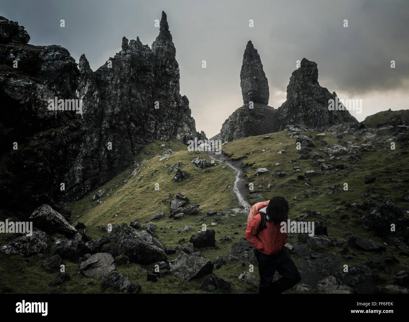 Zwei Personen mit Rucksäcken auf einem schmalen Pfad steigt zu einer dramatischen Landschaft von Felsen Zinnen Stockbild