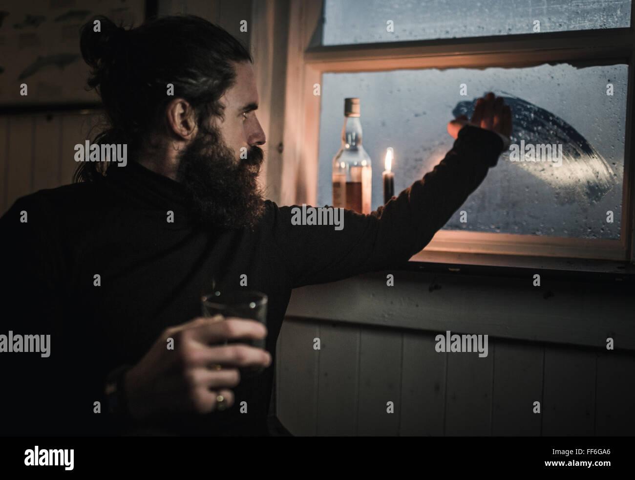 Ein Mann sitzt allein in einem Zimmer mit einer Flasche Whisky und ein Glas Fenster Kondenswasser abwischen Stockbild