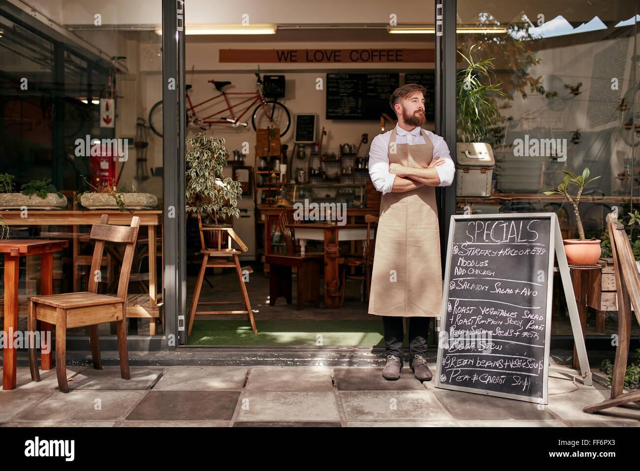Porträt eines jungen Mannes stand vor seinem Café. Junger Mann mit Bart trägt eine Schürze stehen Stockbild